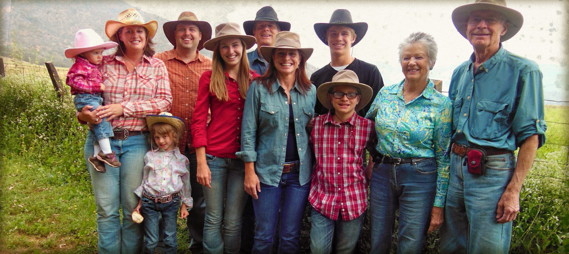 A family of three generations stands for a group photo while enjoying a dude ranch vacation.