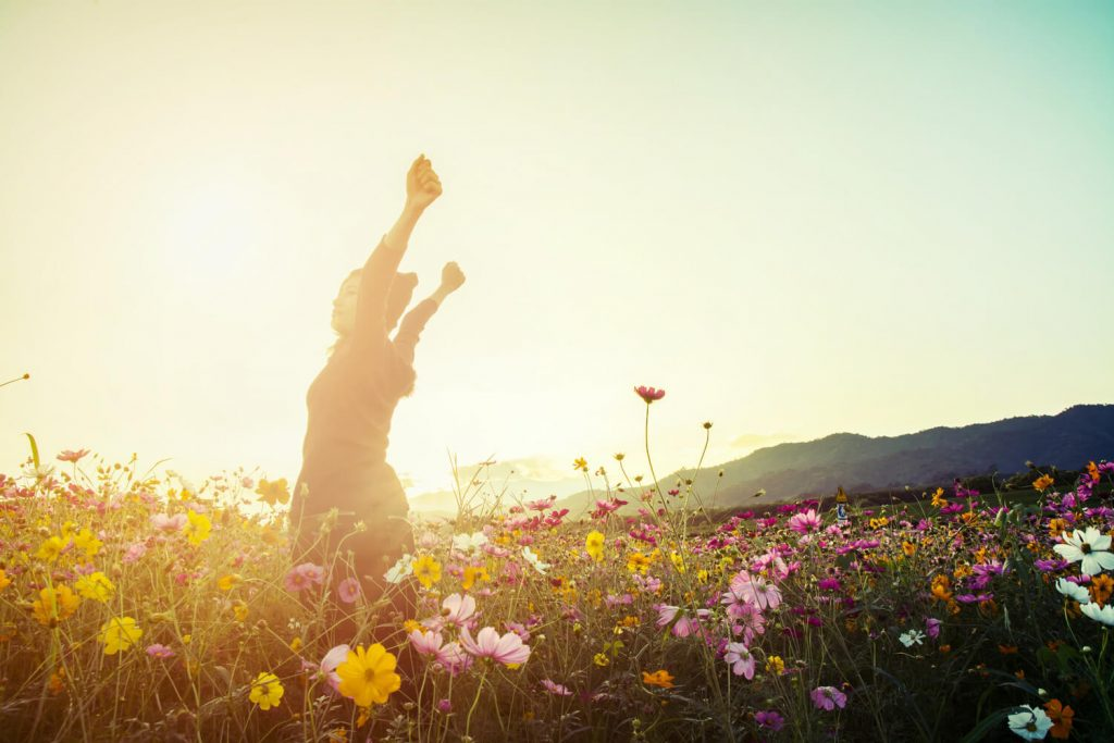 A young woman raises her arms in jubilation as she enjoys her ranch getaway in Kern County California.